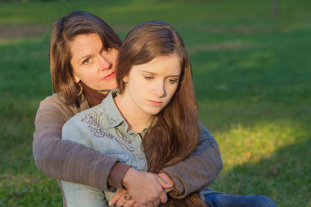 Concerned European mother holding depressed daughter outdoors