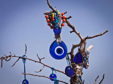 good luck charm: Evil eye hanging from a branch in Cappadocia Turkey