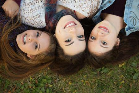Trio of happy teenage girls laying down on grass