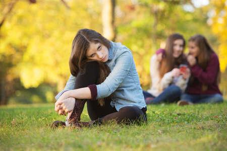 persona triste: Chica solitaria apoyada en la rodilla delante de adolescentes hablando Foto de archivo