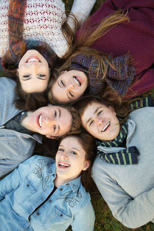 laying down: Group of five Caucasian teenagers laying down on grass together Stock Photo