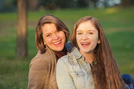 Laughing cute mother and female teenager sitting together Stockfoto
