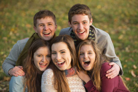Five laughing white teenage males and females together