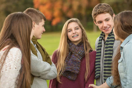 Smiling Caucasian teen female with group of friends Standard-Bild