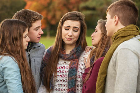 Crying teen in scarf with sympathetic friends outdoors