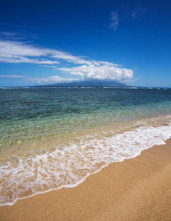 View of Maui in clouds from Molokai Beach