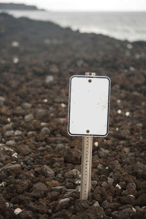volcanic rock: Blank white sign on beach of volcanic rock