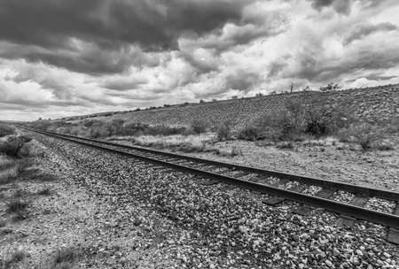 monsoon clouds: Empty railroad tracks with monsoon clouds in black and white
