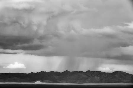 monsoon clouds: Distant storm along mountain range in Arizona