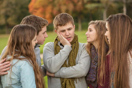 mourn: Young male teen with confused expression and friends