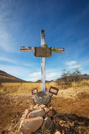 grave site: Old shallow stone grave with crucifix and blank frames