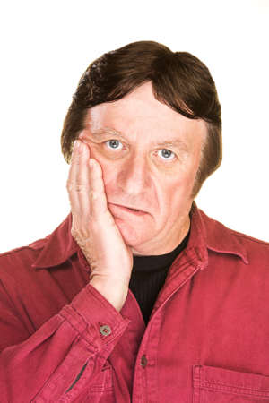 despairing: Despairing mature man with hand on cheek over white Stock Photo