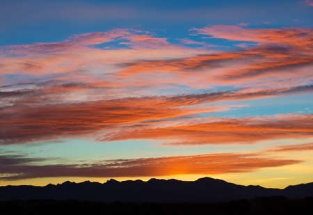 breaking through: Sunrise breaking through sky above mountain range