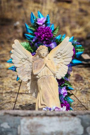 Outdoor graf marker met florale decoratie en stenen engel