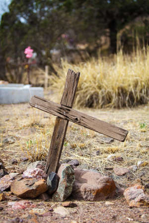 worn out: Worn out wooden asymmetrical crucifix grave marker in desert Stock Photo