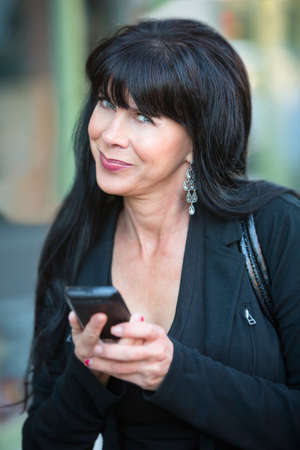 relieved: Business woman with long dark hair using smart phone