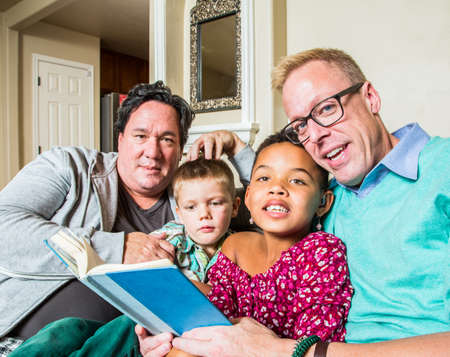 same sex: An attractive gay couple reads to their children in living room