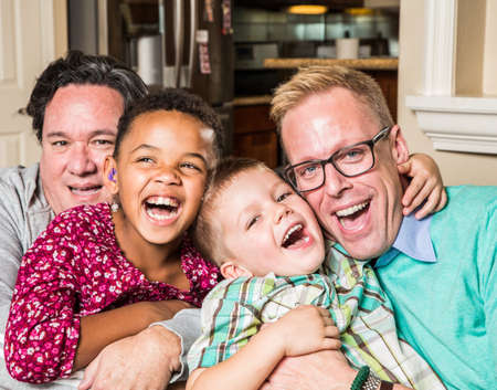 Gay parents and their children pose for a photo at home