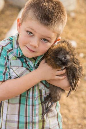 farm boys: Smiling boy outside hugs his pet chicken