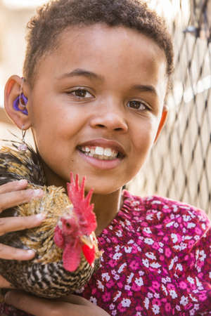 Cute African girl with hearing aid holding a rooster