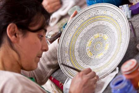 adds: CAPPADOCIA, TURKEY – APRIL 17: Artist adds detail to a ceramic bowl with animal design patternon April 17, 2012 in Cappadocia, Turkey.