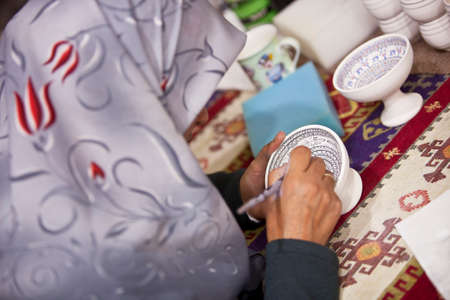 decorates: CAPPADOCIA, TURKEY – APRIL 17: Woman decorates a ceramic bowl with designs typical to the region on April 17, 2012 in Cappadocia, Turkey. Editorial