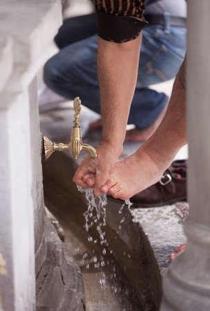 feet washing: Muslim man in Turkey washing his feet in public fountain