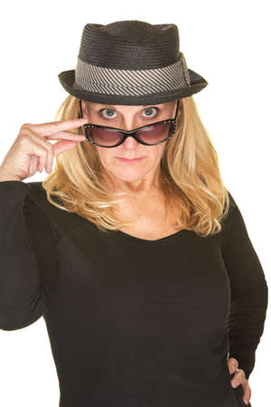 looking over: Cute woman in black with hat looking over sunglasses