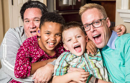 Gay parents pose with their childen in the living room Stockfoto