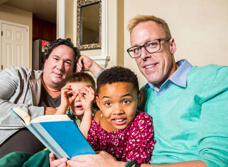 Attractive gay couple reads a book to their children