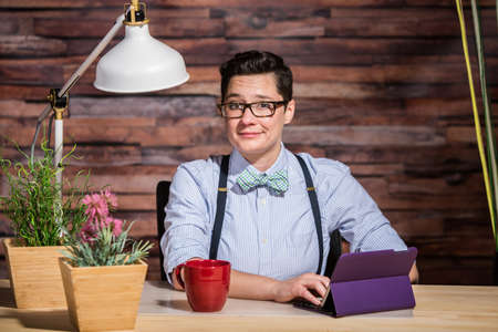 Flattered dapper woman with bowtie at desk with a red coffee cup