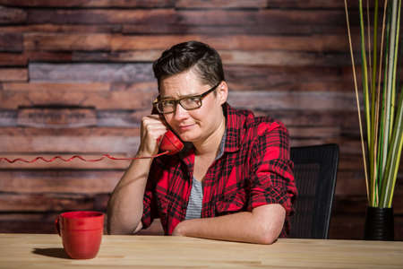 yuppie: Woman wearing flannel shirt on push-button phone seated in front of modern desk at hipster office