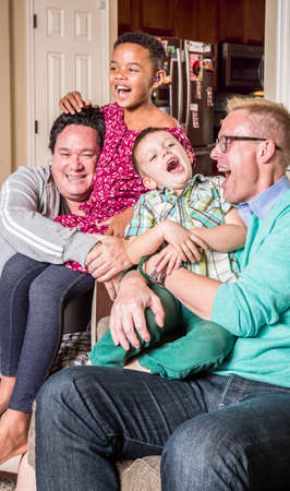 Gay parents in the living room laugh with their children Foto de archivo