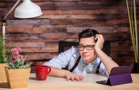 yuppie: Disappointed lesbian businesswoman leaning against arm at desk