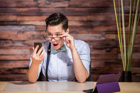dapper: Surprised dapper businesswoman looking over eyeglasses at phone