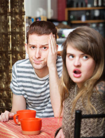 aggravated: Frustrated young man sitting in cafe with woman