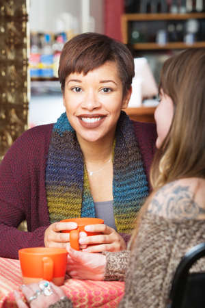 indoors: Smiling young adult with friend at coffee house indoors Stock Photo