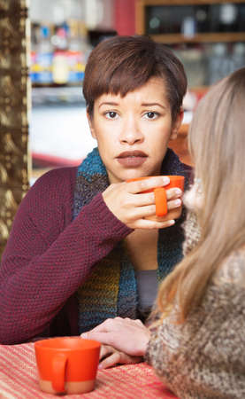 apologetic: Sympathetic woman with friend at coffee house indoors Stock Photo