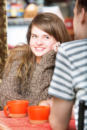 flattered: Happy woman staring at man in cafe