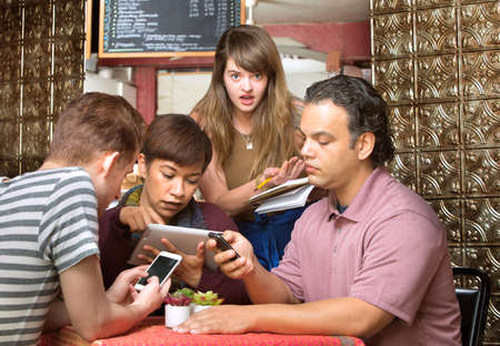 ignoring: Rude diners ignoring waitress in a coffee house
