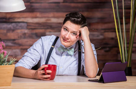dapper: Woman with eyeglasses in hand at stylish office desk with a red cup Stock Photo