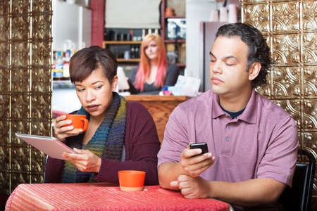 peek: Young adult couple at cafe sneaking a peek at their devices