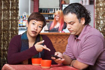 novios enojados: Mujer enfadada apuntando al teléfono celular a cabo por el hombre Foto de archivo