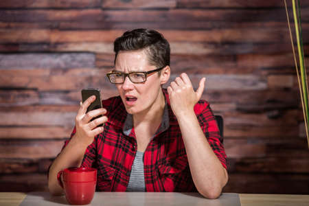 front desk: Serious woman wearing flannel shirt looking at smart phone and seated in front of modern desk at hipster office