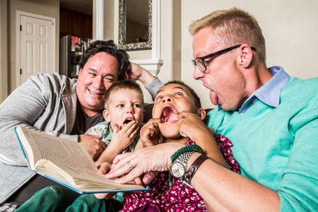 Homosexual parents reading and making faces with son and daughter