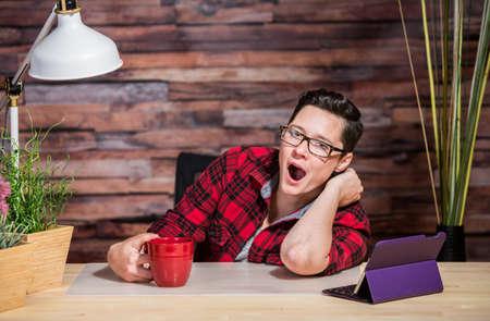yuppie: Yawning Caucasian boyish female at desk with tablet computer