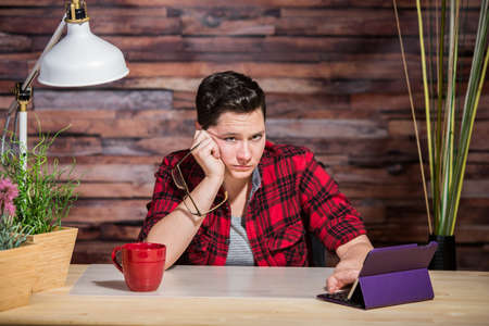 Single bored butch lady at desk with tablet computer