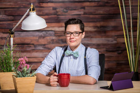 lesbian: Strict boyish woman in suspenders at desk with a red coffee cup