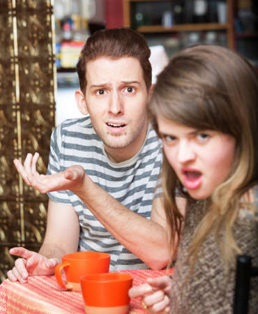 disgusted: Disgusted young woman with frustrated man at cafe Stock Photo