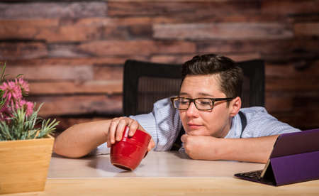 looking into: Bored woman with eyeglasses looking into cup Stock Photo